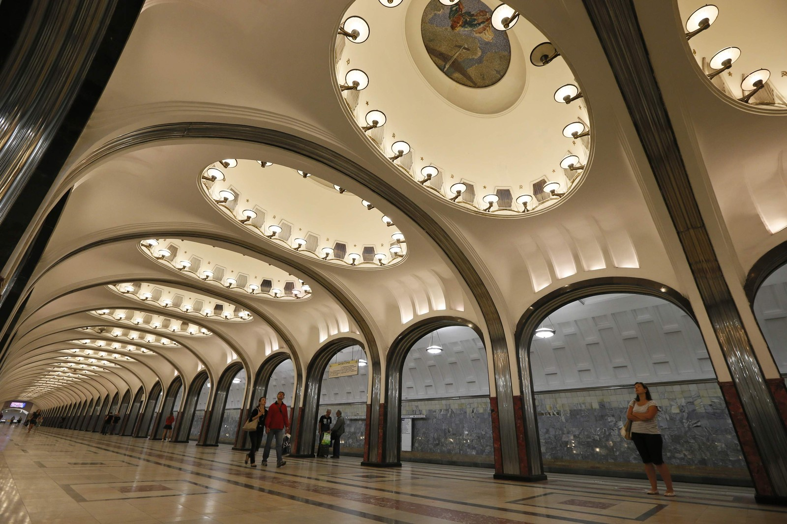People wait for the train in Mayakovskaya metro station, which was built in 1938, in Moscow August 17, 2013. The Moscow metro was opened in 1935, and carries more passengers daily than the London and New York metro systems combined. REUTERS/Lucy Nicholson (RUSSIA - Tags: SOCIETY TRANSPORT)