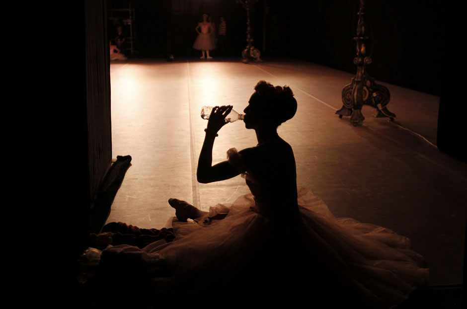 A Cuban National Ballet ballerina drinks water during the Cuban National Ballet Gala concert at the Bolshoi Theatre in Moscow, August 2, 2011. Cuban ballet dancers performed several pieces from Coppelia, The Swan Lake, Don Quixote in honor of Alicia Alonso, Cuba's prima ballerina assoluta and director of the Cuban National Ballet. REUTERS/Denis Sinyakov (RUSSIA - Tags: SOCIETY IMAGES OF THE DAY)